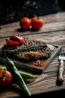 Bistecca alla griglia con coltello e forchetta scolpiti su pietra nera ardesia. bistecca su una pietra di marmo calda. copia spazio, sfondo scuro, foto di moda di cibo.