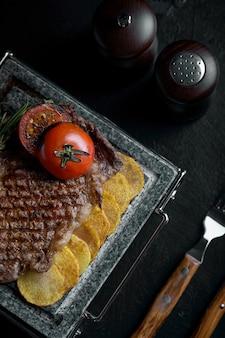 Bistecca alla griglia con coltello e forchetta scolpiti su pietra nera ardesia