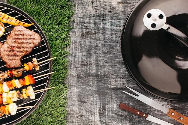 Bistecca alla griglia e spiedini di carne sulla forcella metallica grill barbecue
