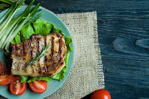 Bistecca alla griglia servita su un piatto, decorata con spezie per carne, rosmarino, verdure e verdure su un legno scuro
