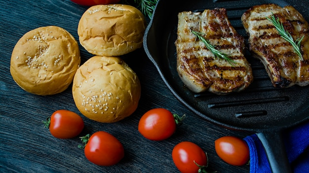 Bistecca alla griglia su una teglia rotonda, guarnita con spezie per carne, rosmarino, verdure e verdure su un fondo di legno scuro.