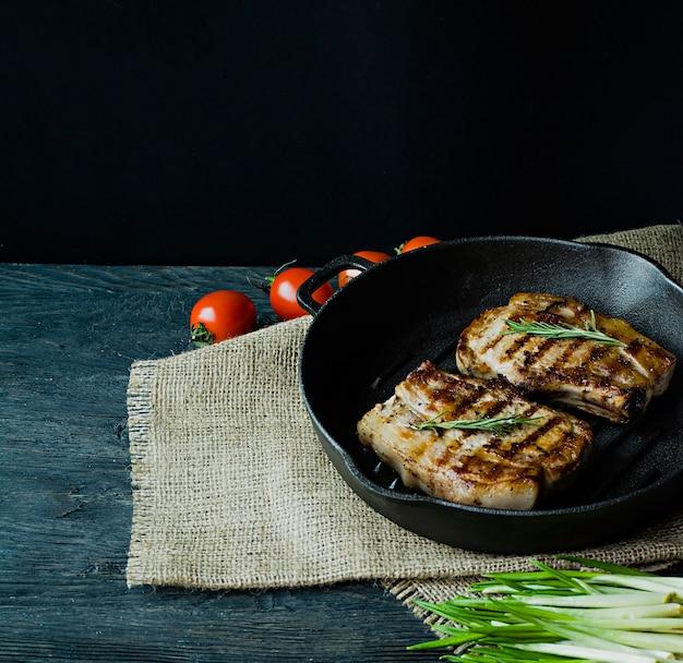 Bistecca alla griglia su una teglia rotonda, guarnita con spezie per carne
