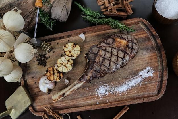 Bistecca alla griglia sulla tavola di legno aglio sale rosmarino