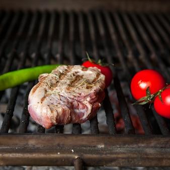 Bistecca arrostita del primo piano bistecca arrostita con orizzontale del pepe e del pomodoro