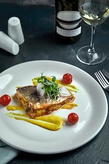 Bistecca bianca di pesce grigliato sul cuscino di verdure e salsa gialla, con pomodori ed erbe fresche. peschi sul piatto bianco con vino bianco su bello fondo scuro. avvicinamento. spazio