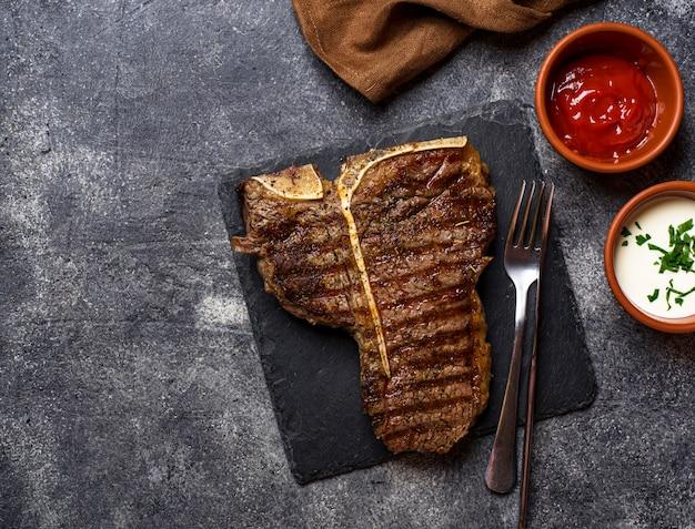 Bistecca con l'osso alla griglia su oscurità