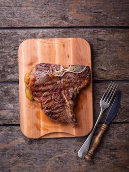 Bistecca con l'osso arrostita sul bordo di legno