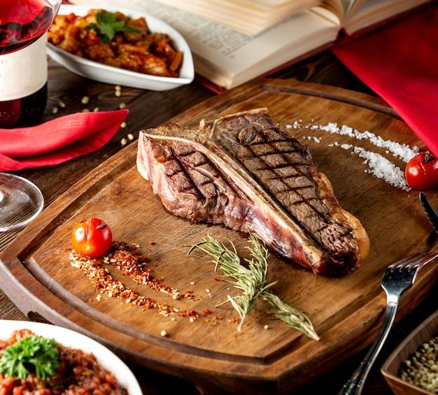 Bistecca con l'osso servita in tavola di legno con stecca di rosmarino