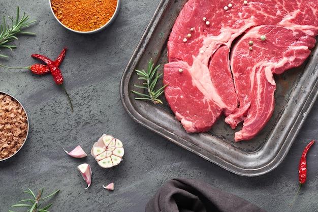 Bistecca cruda. carne con spezie ed erbe aromatiche