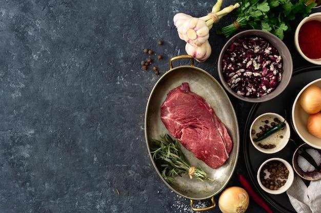 Bistecca cruda con ingredienti per cucinare vista dall'alto di cibo sano