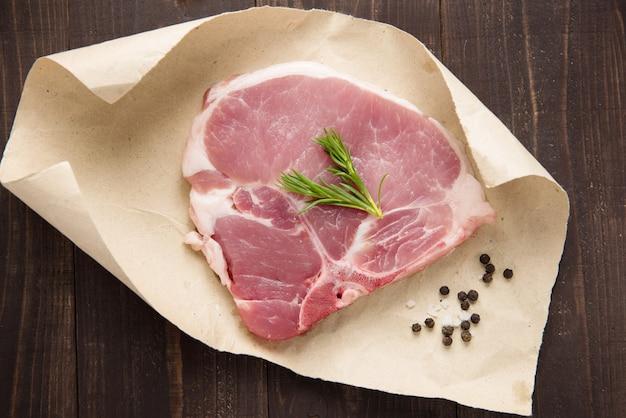 Bistecca cruda di braciola di maiale su carta su legno