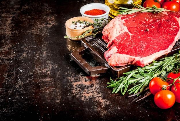 Bistecca di agnello cruda fresca su un tagliere, con ingredienti per cucinare