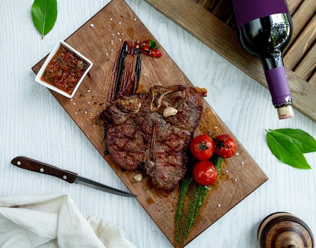 Bistecca di agnello servita con salsa, pomodori grigliati