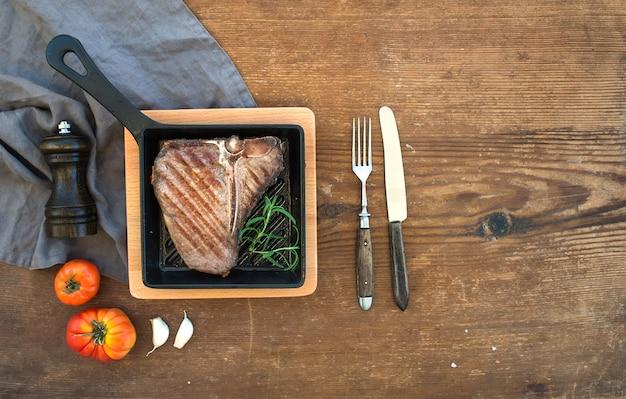 Bistecca di bistecca con l'osso cotta con spicchi d'aglio, pomodori, rosmarino, pepe e sale in una piccola padella