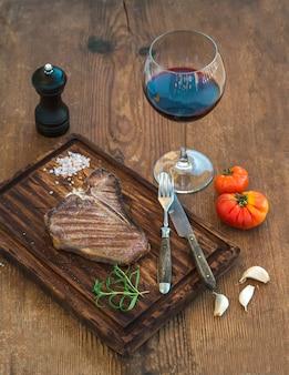 Bistecca di bistecca con l'osso cotta sulla tavola di servizio con spicchi d'aglio, pomodori, rosmarino, spezie e bicchiere di vino rosso sul tavolo di legno rustico