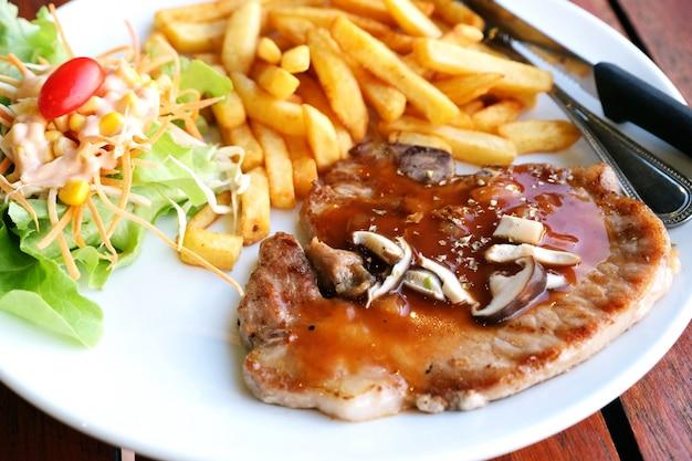 Bistecca di braciola di maiale del primo piano con insalata e frenchfried