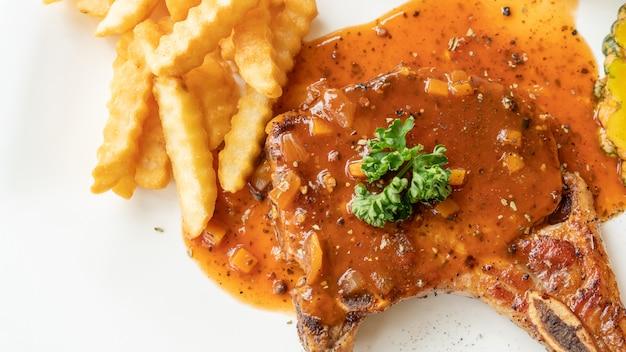 Bistecca di braciola di maiale su un piatto bianco.