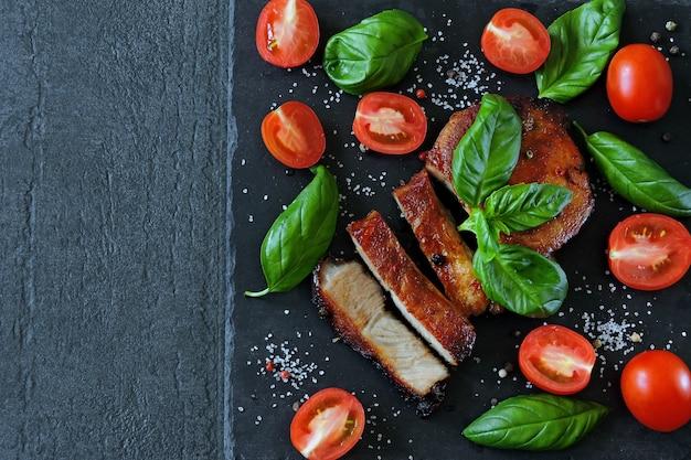 Bistecca di carne appetitosa fresca su una tavola con pomodori e basilico.