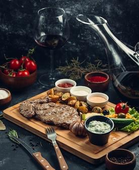 Bistecca di carne con verdure e varietà di salse su una tavola di legno.