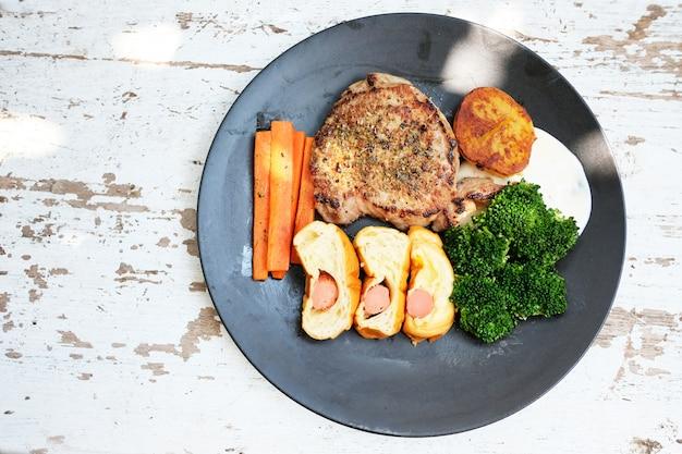 Bistecca di carne con verdure grigliate e spezie collocati in un piatto su un tavolo di legno