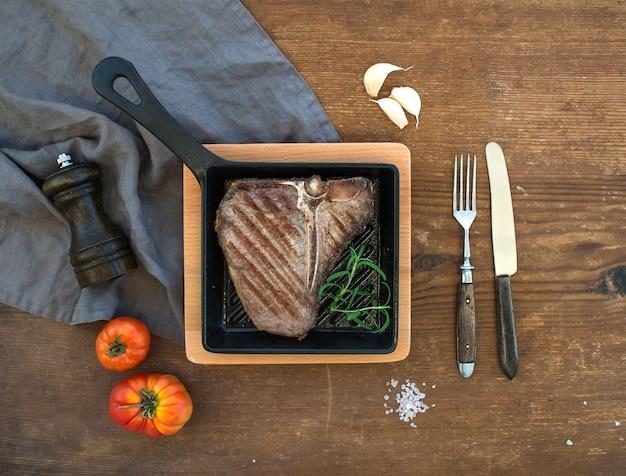 Bistecca di carne cotta in una piccola padella sul tavolo di legno rustico