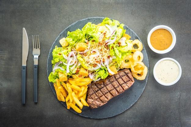 Bistecca di carne di manzo alla griglia con anello di cipolla di patatine fritte