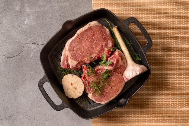 Bistecca di carne fresca cruda sulla griglia padella di ferro, condimento e forchetta di carne su legno