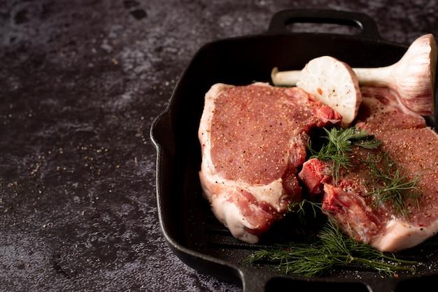 Bistecca di carne fresca cruda sulla griglia padella di ferro, condimento e forchetta di carne
