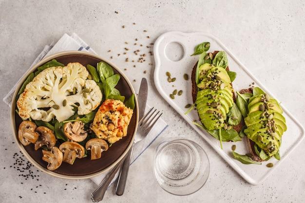 Bistecca di cavolfiore con champignons alla griglia e hummus e toast di avocado, vista dall'alto.
