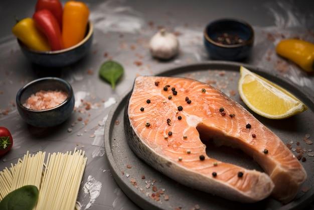 Bistecca di color salmone dell'angolo alto sul vassoio con gli ingredienti