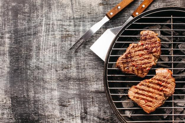 Bistecca di contorno fritto sulla griglia del barbecue sul vecchio contesto
