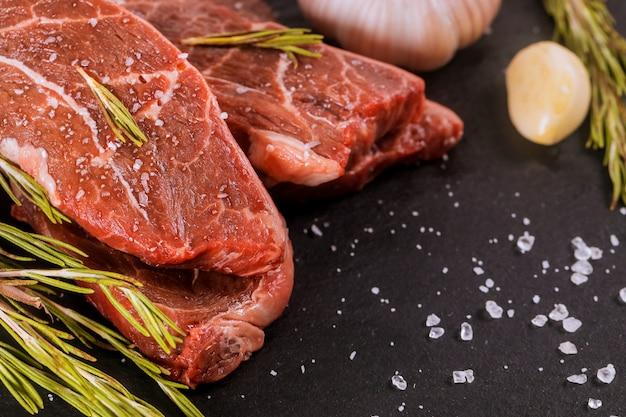 Bistecca di controfiletto cruda con rosmarino e aglio, sale e pepe sopra il tavolo di pietra.