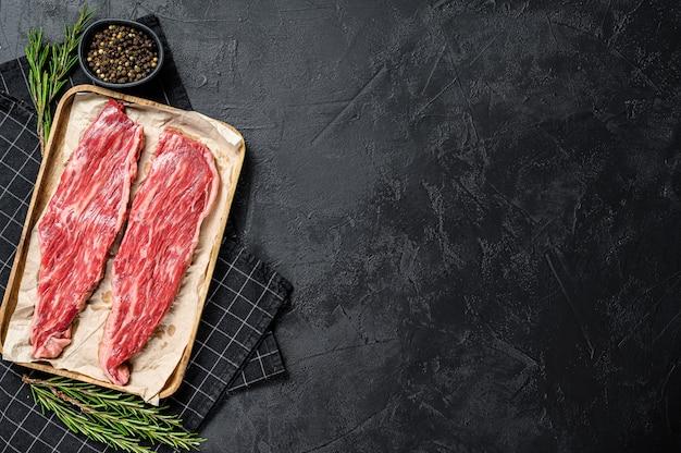Bistecca di fianco cruda. filetto di manzo marmorizzato sullo sfondo