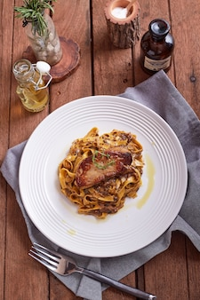 Bistecca di foie gras alla griglia con con le fettuccine sul tavolo del ristorante
