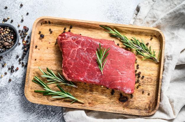Bistecca di lombo crudo striscia su un vassoio di legno. carne di manzo. vista dall'alto.