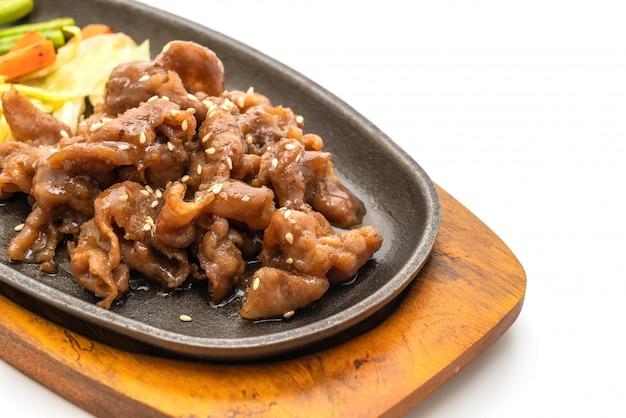 Bistecca di maiale affettato sulla piastra riscaldante