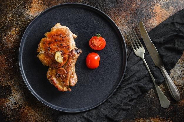 Bistecca di maiale alla griglia con condimenti con forchetta e coltello