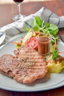 Bistecca di maiale alla griglia con purè di patate su un primo piano piatto.