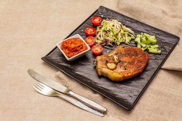 Bistecca di maiale alla griglia con salsa di pomodoro e insalata di insalata di cavolo