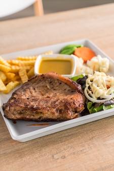 Bistecca di maiale con patatine fritte e insalata