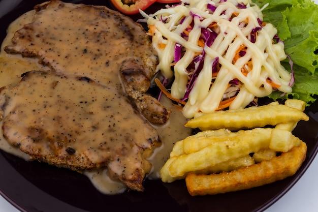 Bistecca di maiale con pepe nero in piatto nero