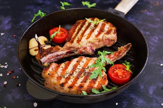 Bistecca di maiale cruda con erbe sulla superficie scura. bistecca succosa cruda sull'osso