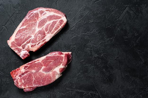Bistecca di maiale cruda con l'osso. carne grigliata. sfondo nero. vista dall'alto. spazio per il testo