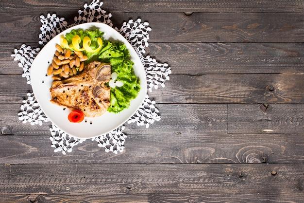 Bistecca di maiale cucinata in casa con spezie foglie di lattuga sul tagliere di legno e un piatto,