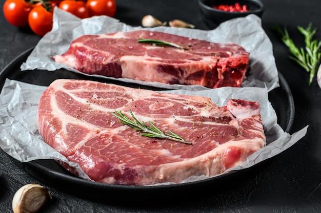 Bistecca di maiale fresca. carne di marmo su carta pergamena. sfondo nero. vista dall'alto