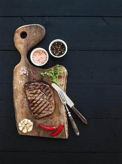 Bistecca di manzo alla griglia con erbe e spezie sul tagliere di noce su sfondo nero in legno