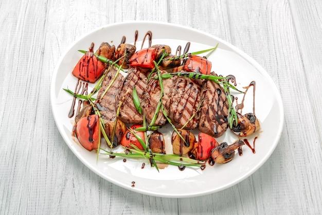 Bistecca di manzo alla griglia con funghi e pomodori