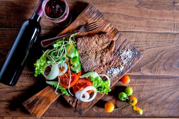 Bistecca di manzo alla griglia e sale su un tagliere di legno
