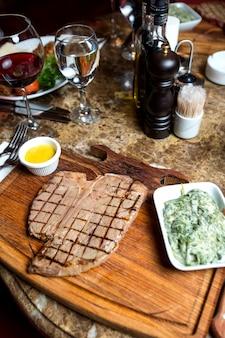 Bistecca di manzo alla griglia servita con erbe e miscela di yogurt