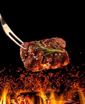 Bistecca di manzo che cade sulla griglia con il fuoco.